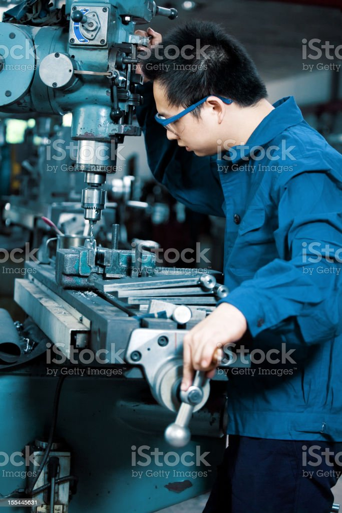 Man in workshop using drill royalty-free stock photo