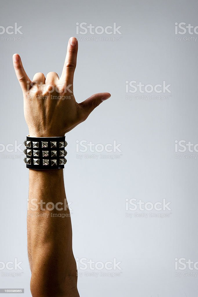 Man in Wristband making Rock & Roll Hand Symbol stock photo