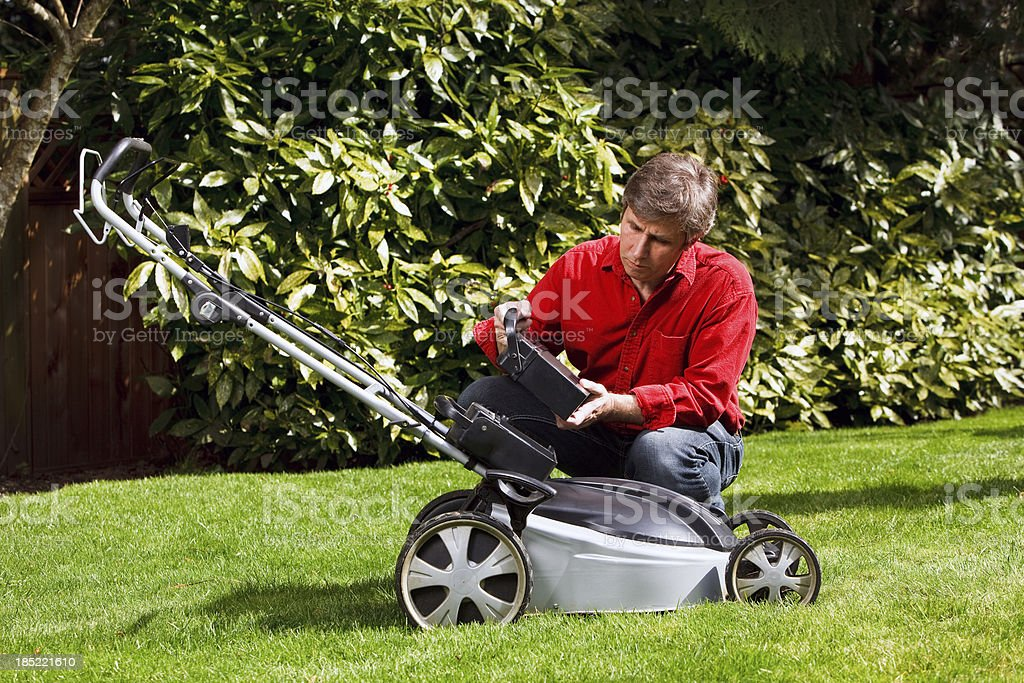 Man in yard installing rechargeable battery into lawnmower stock photo
