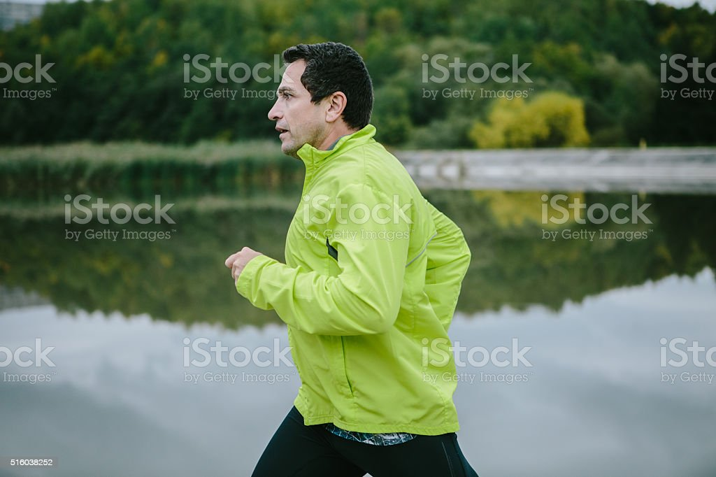 Man in yellow neon jacket runnig at the lake stock photo