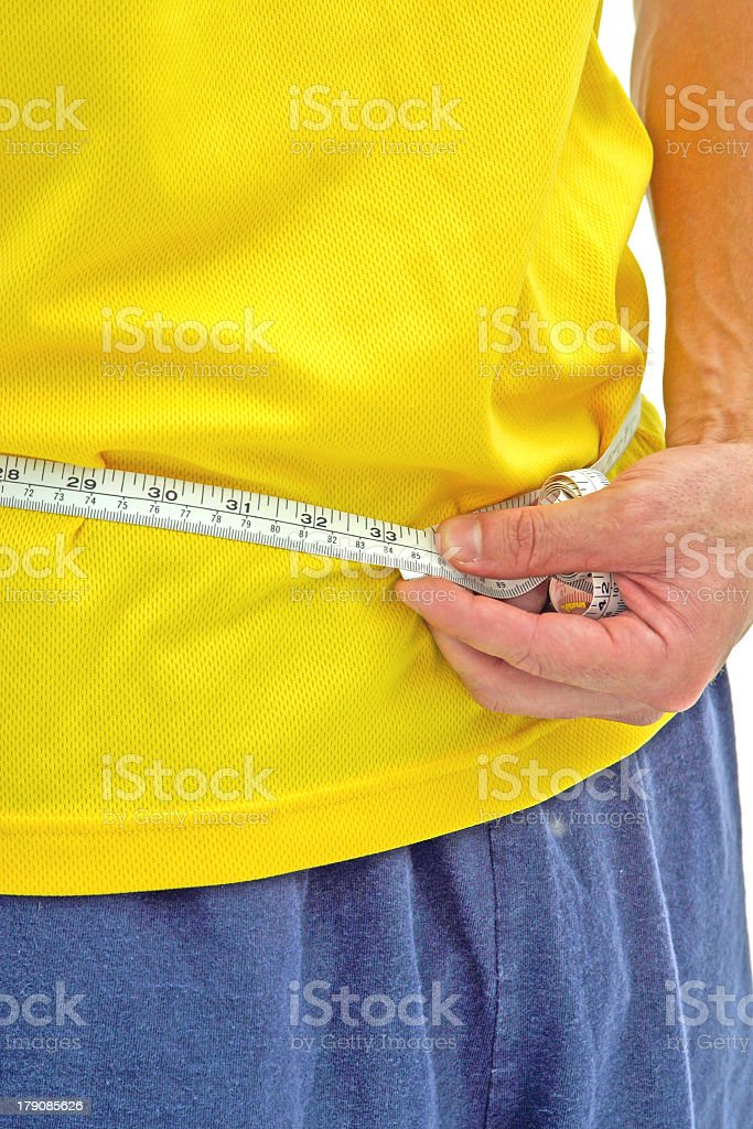 Man in yellow shirt and blue pants measuring waist with tape royalty-free stock photo