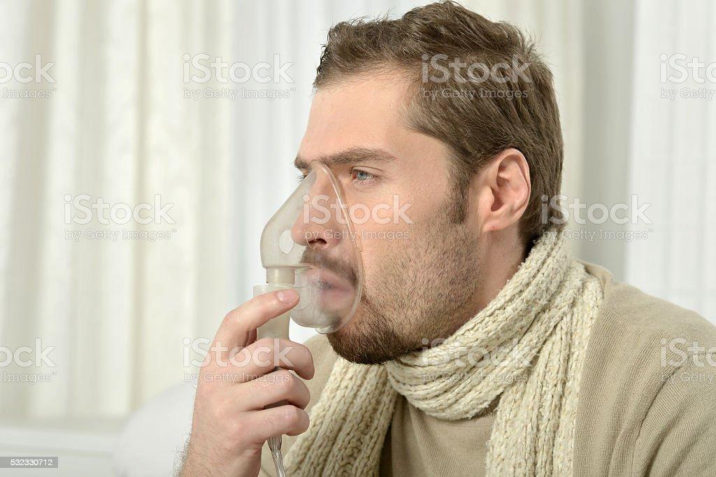 Man Inhaling Through Inhaler Mask stock photo