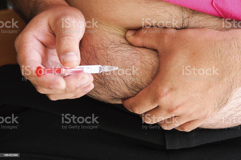 Man inject with a syringe in his stomach close-up. royalty-free stock photo