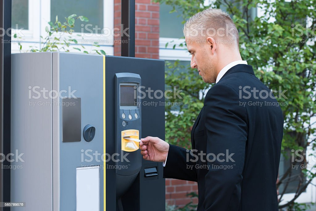 Man Inserting Ticket To Pay For Parking stock photo