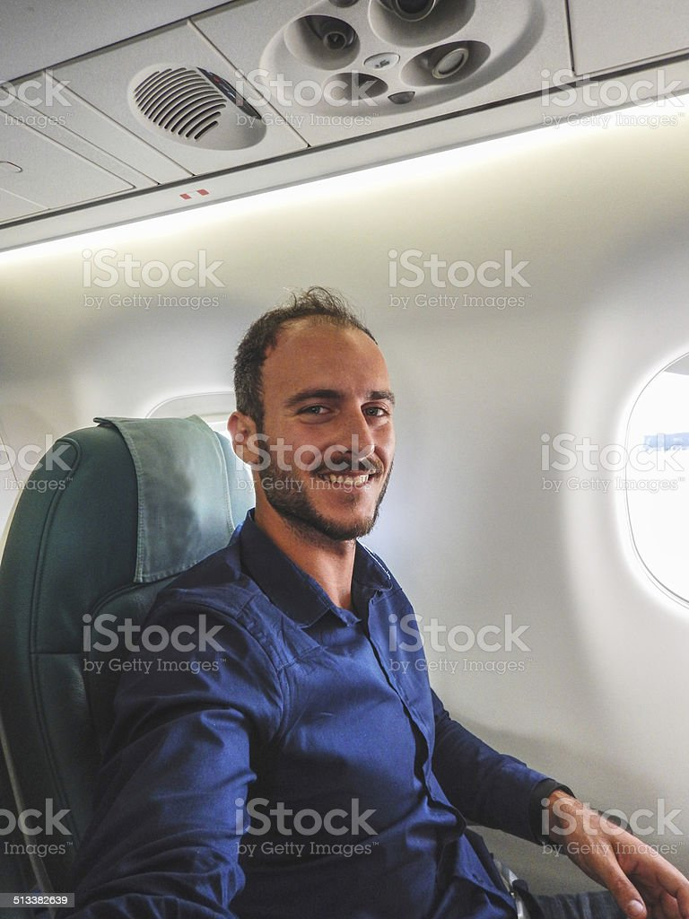 man inside an airplane smiling
