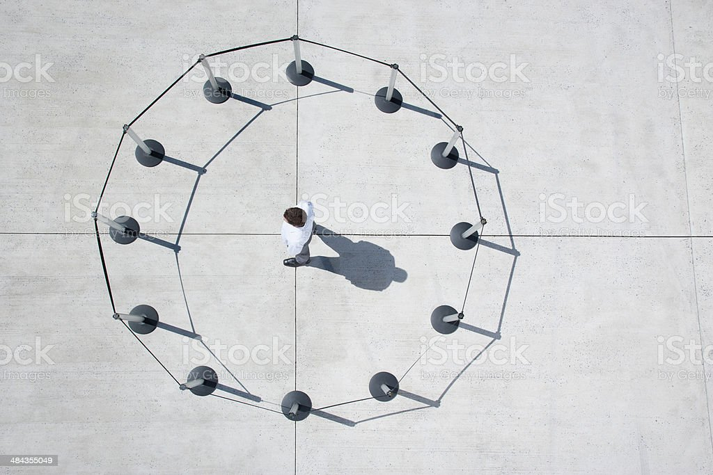 Man inside circle of cordon posts stock photo