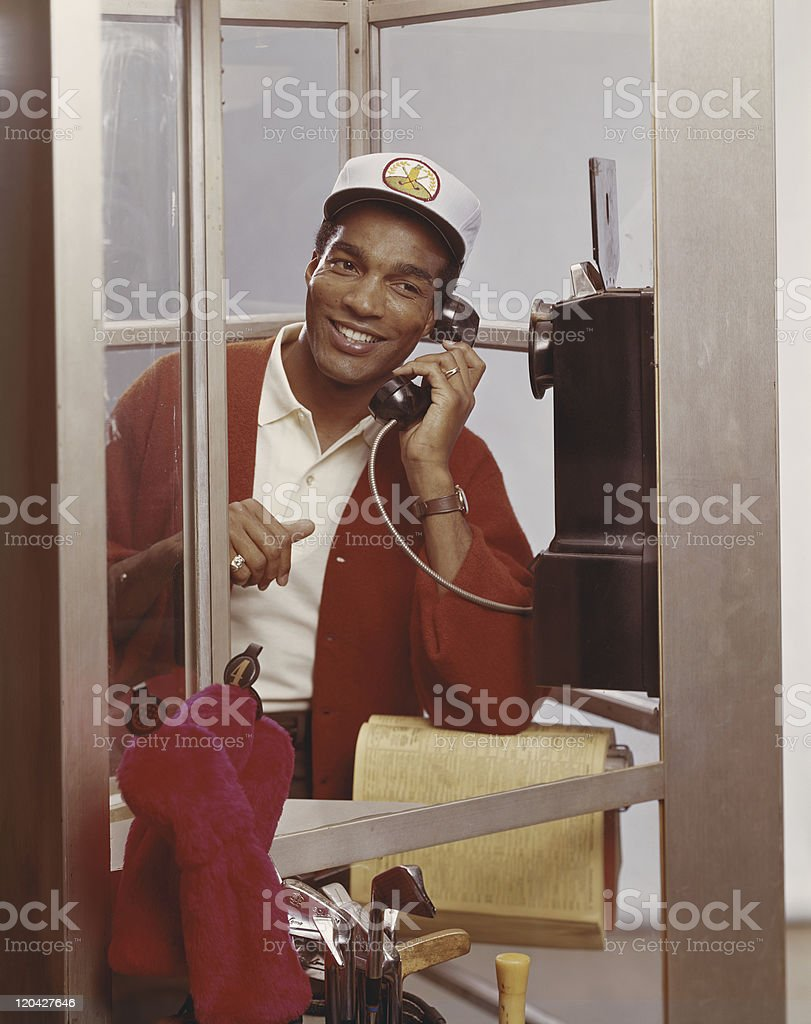 Man inside telephone booth talking on phone stock photo