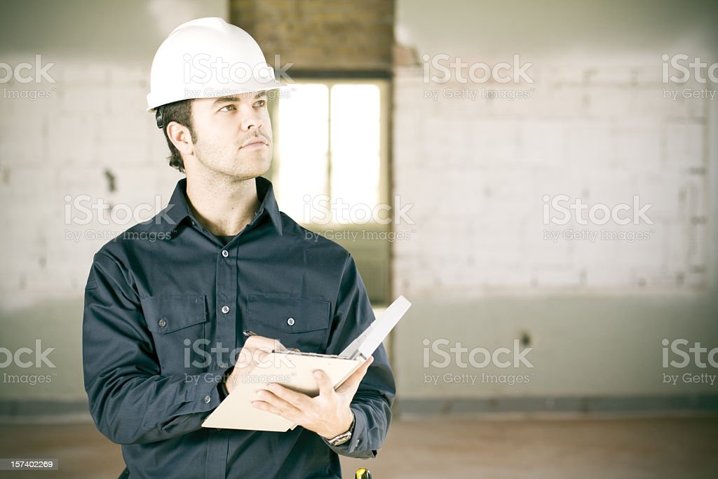 Man inspects building wearing white hard hat stock photo