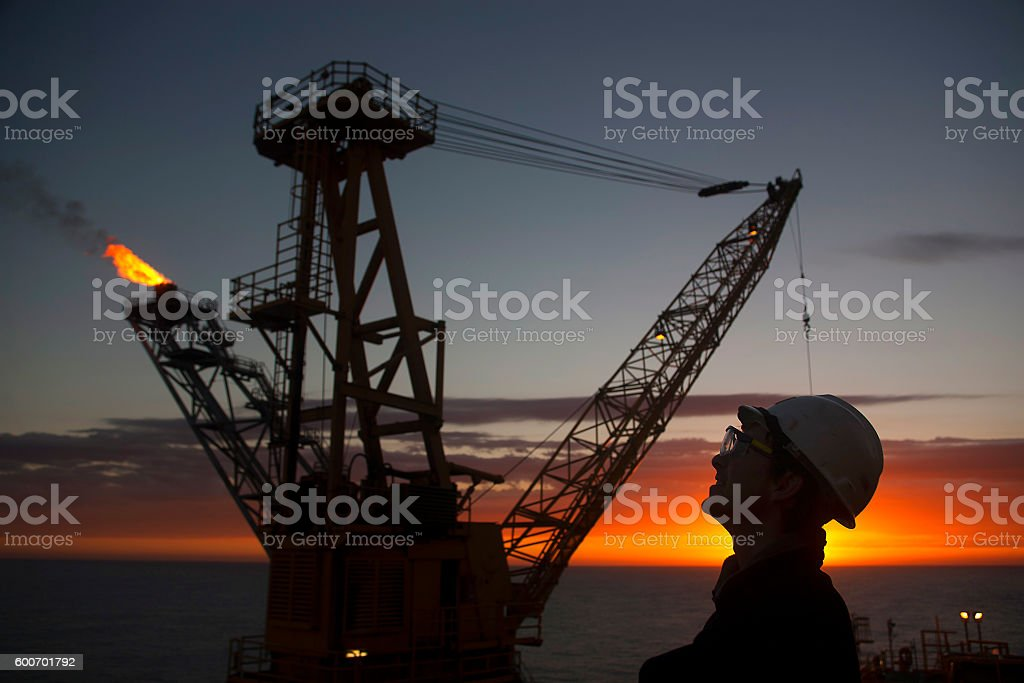 Man inspects oil rig at sunset stock photo