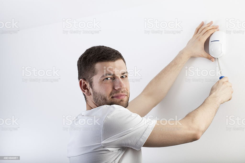 Man installing a security system stock photo