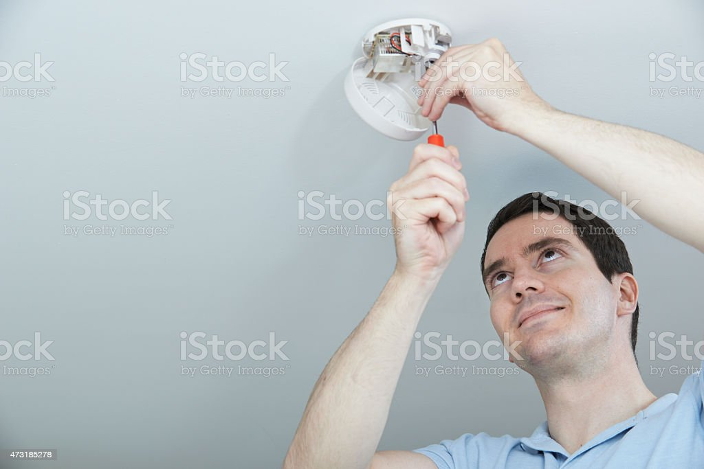 A man installing a smoke detector in a ceiling stock photo
