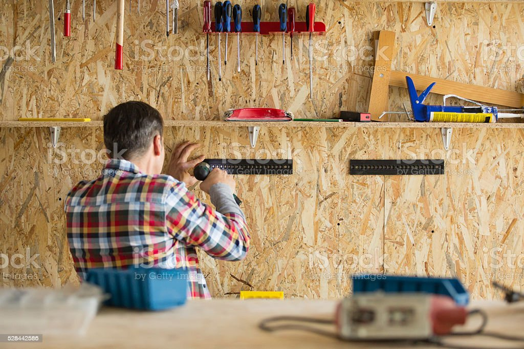 Man installing a tool rack to a wall stock photo