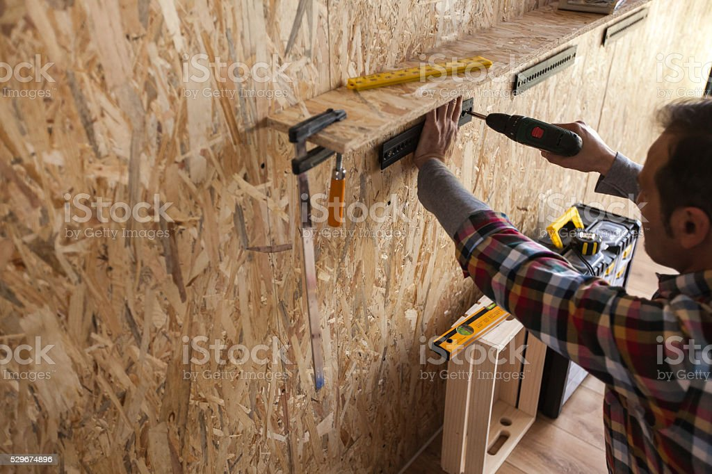 Man installing a tool rack to a wall using cordless drill stock photo
