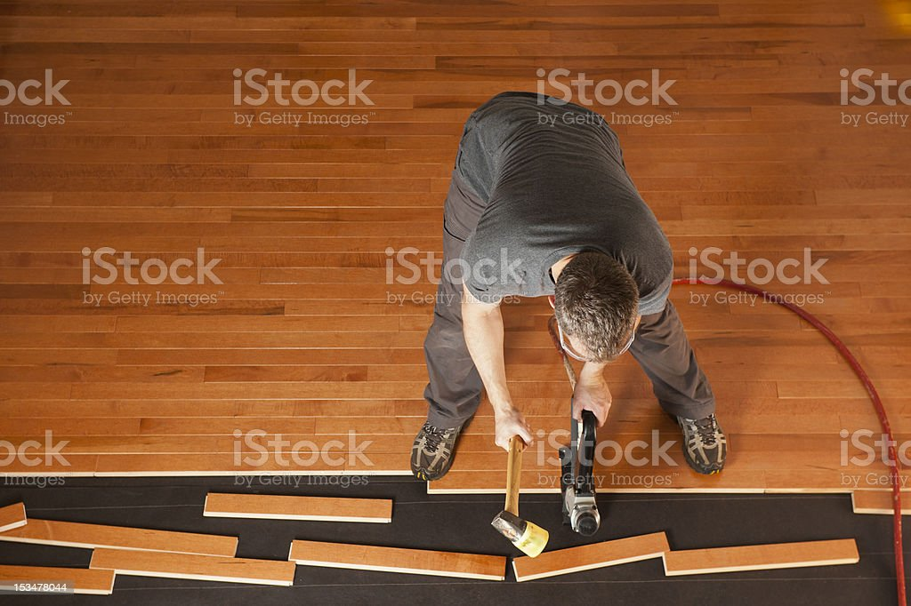 Man installing a wood floor shown from above stock photo