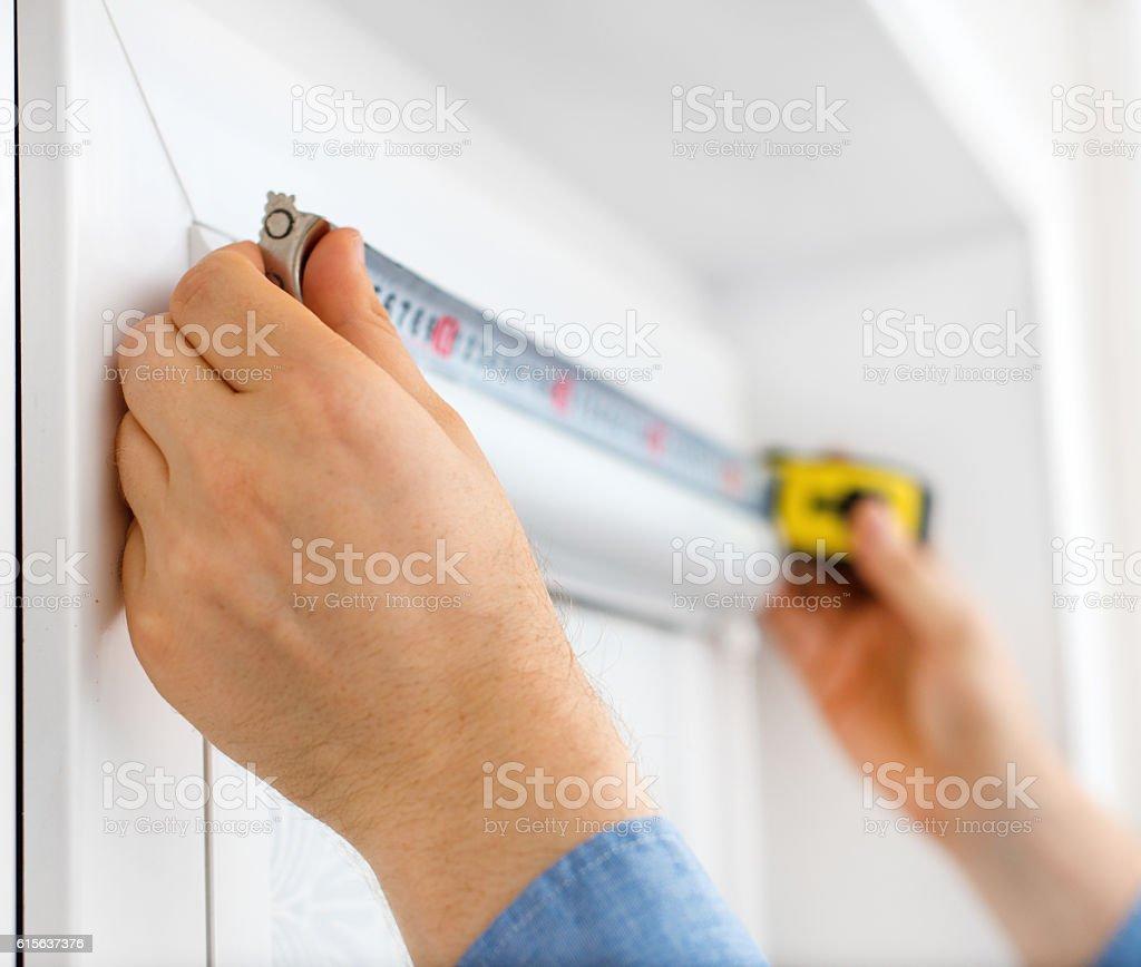 Man installing cassette roller blinds on windows. stock photo