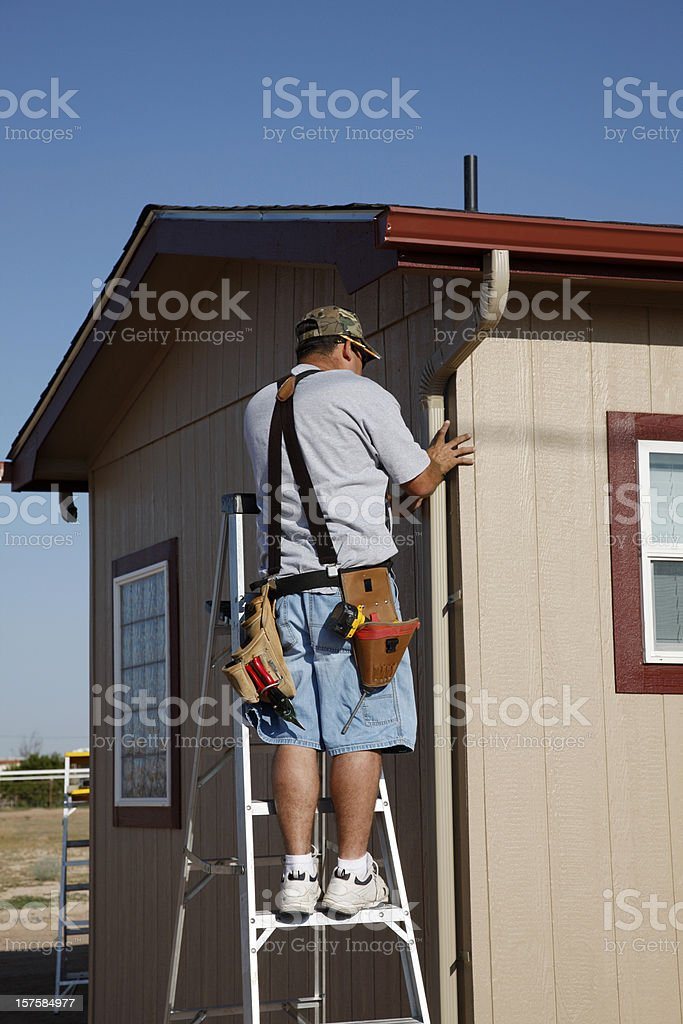 Man Installing Downspout and Seamless Gutters stock photo