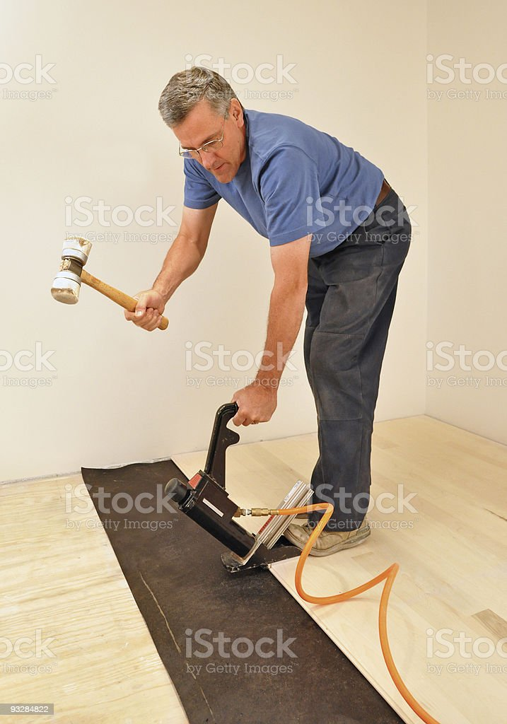 Man installing hardwood floor using power nailer stock photo