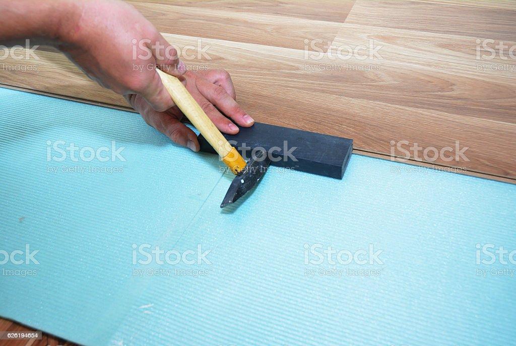 Man Installing New Laminate Wood Flooring. stock photo