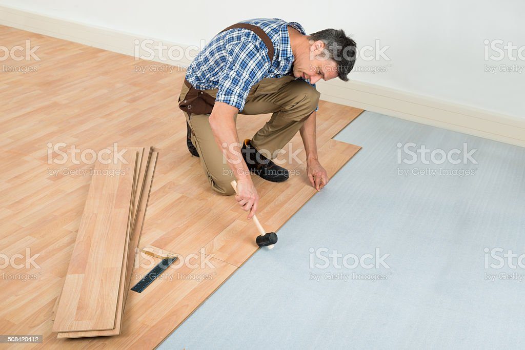 Man Installing New Laminated Wooden Floor stock photo