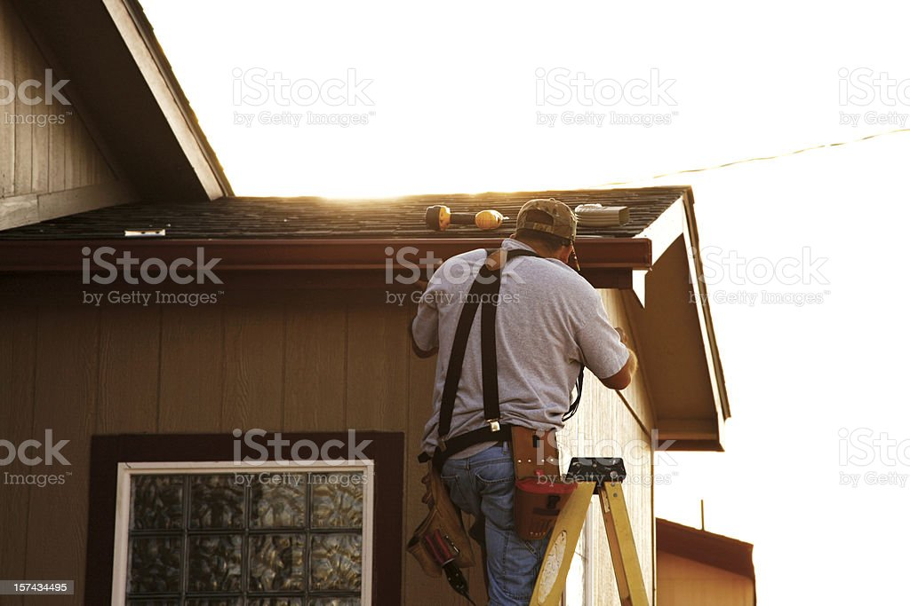 Man Installing Seamless Gutters stock photo
