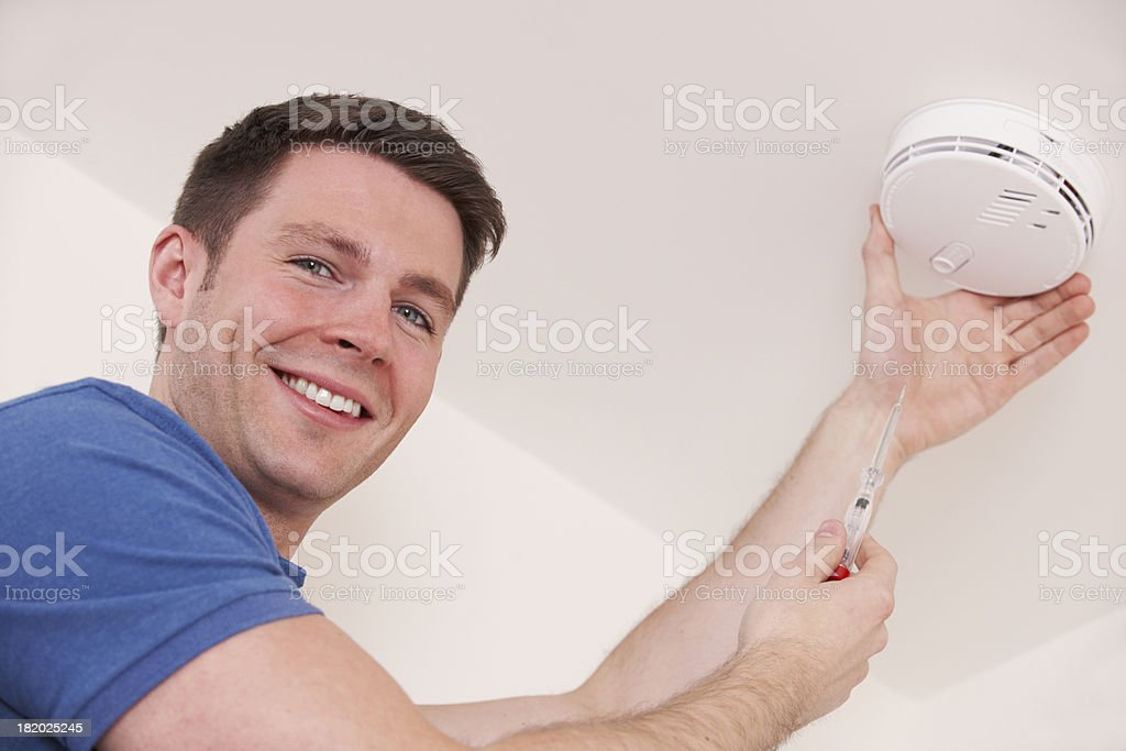 Man Installing Smoke Or Carbon Monoxide Detector stock photo