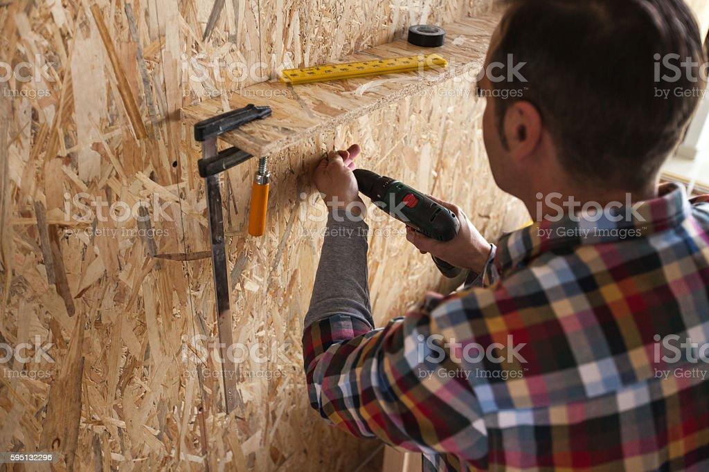 Man installing tool rack stock photo