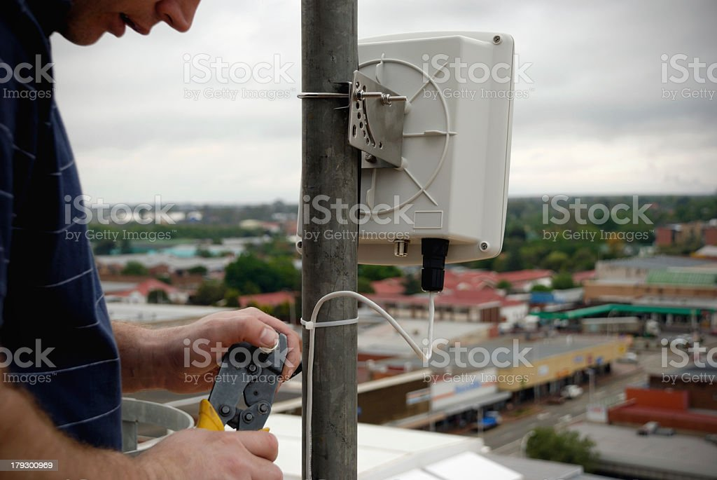 Man installing Wi-Fi apparatus on a rooftop pole stock photo