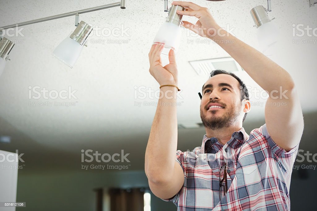 Man installs light fixture in new home stock photo