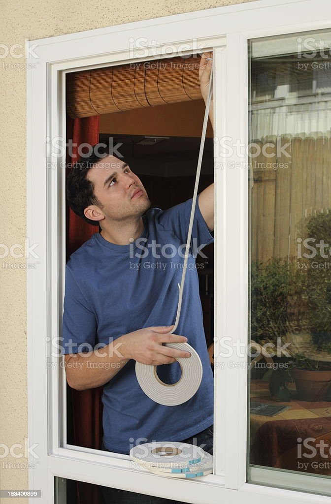 Man Installs Weather Stripping in Window stock photo