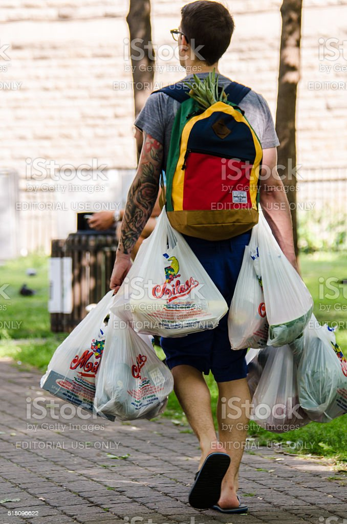 Man invents a clever way to carry many grocery bags stock photo