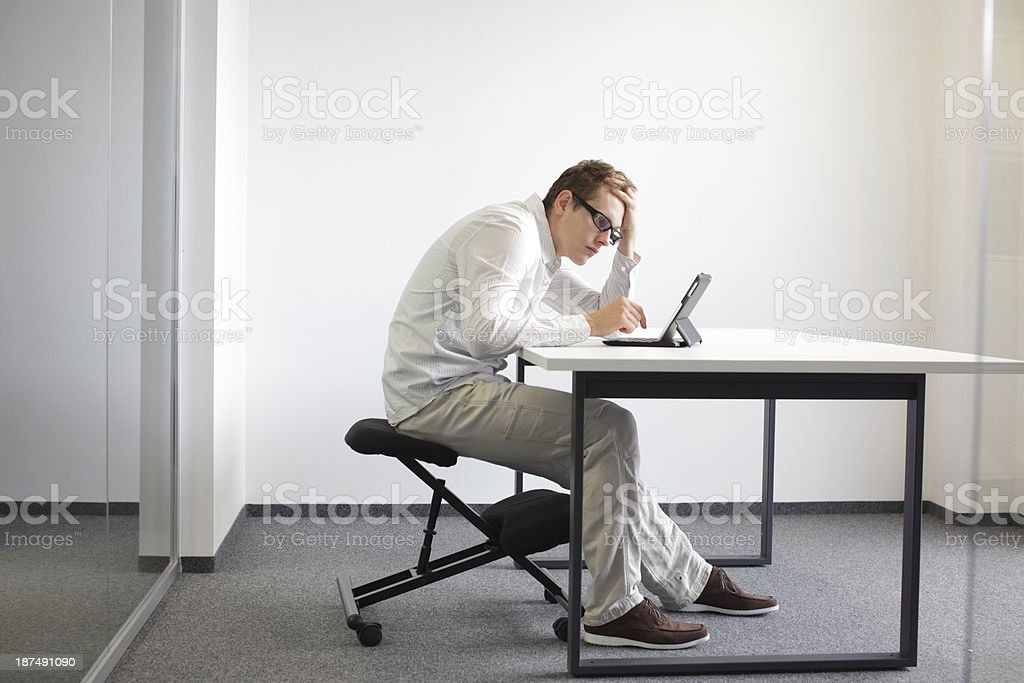 man is bent over  tablet.Bad sitting posture at work stock photo
