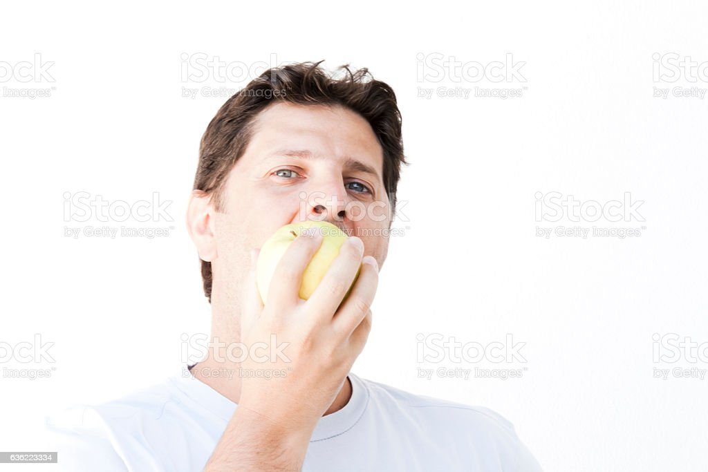 Man is biting an apple stock photo
