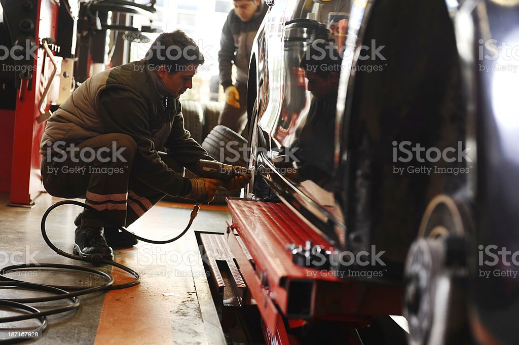 Man is changing tires royalty-free stock photo