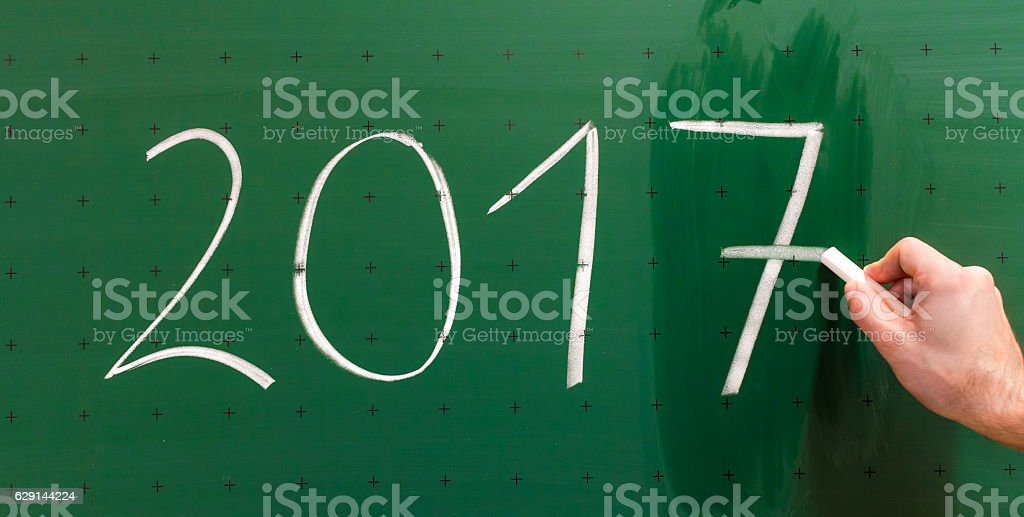 Man is changing year 2016 to 2017 on chalkboard. stock photo