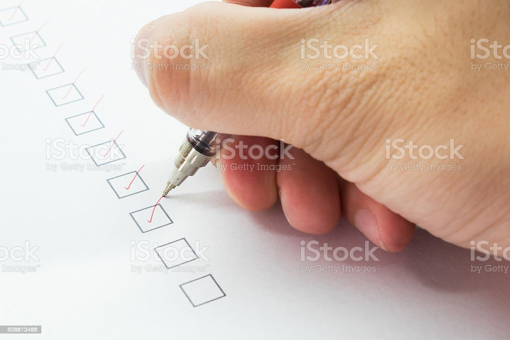 man is checking on list with red pen stock photo