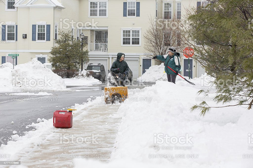 Man is clearing snow with a snowblower stock photo