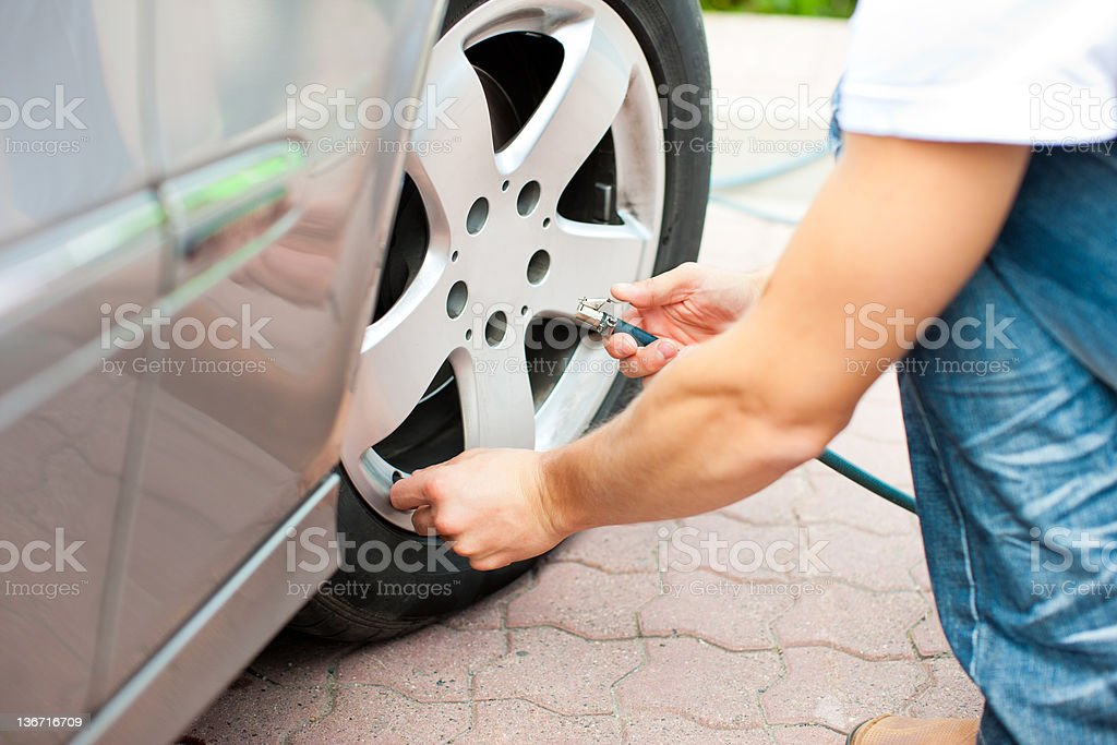 Man is controlling the tire pressure of his car royalty-free stock photo