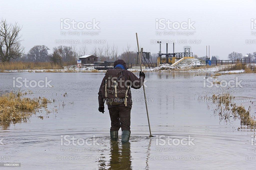 Man is crossing flood water stock photo