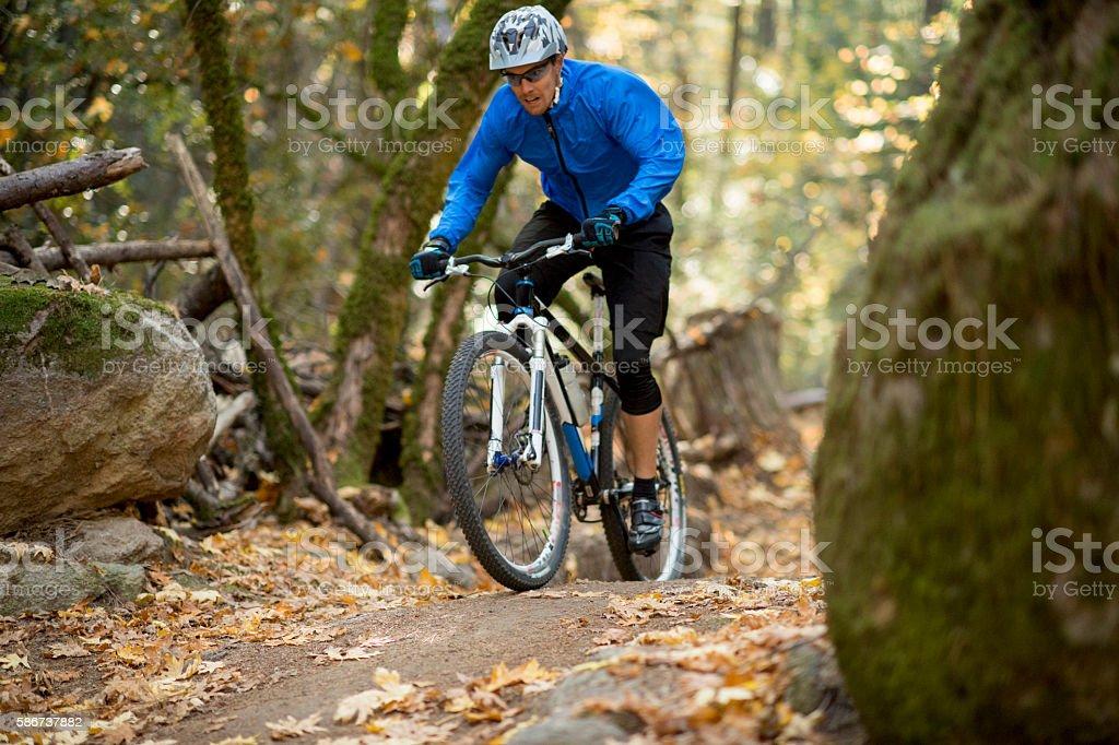 A man is doing extreme mountain biking through the stock photo