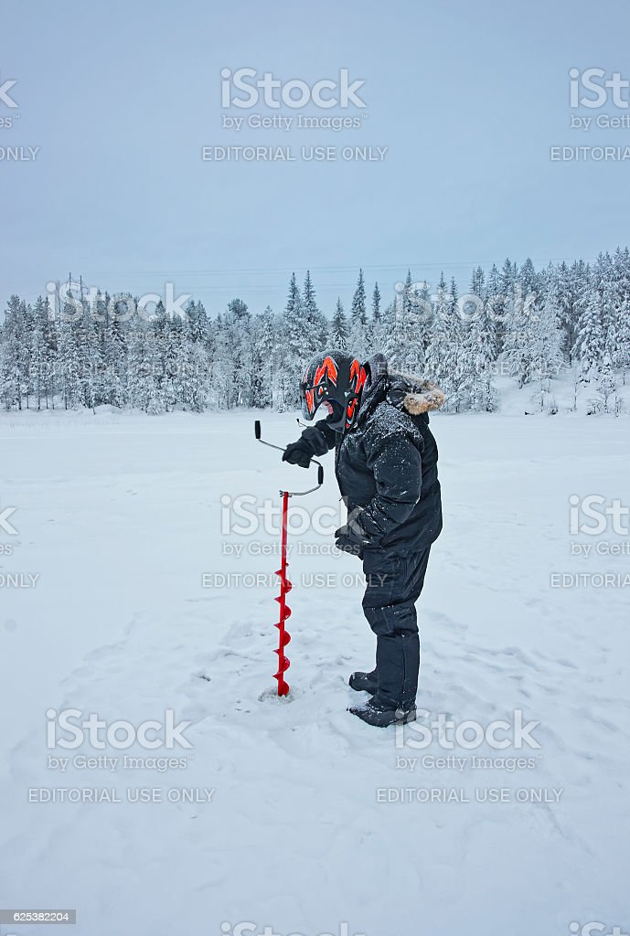 Man is drilling an ice-hole for ice-fishing in Ruka stock photo