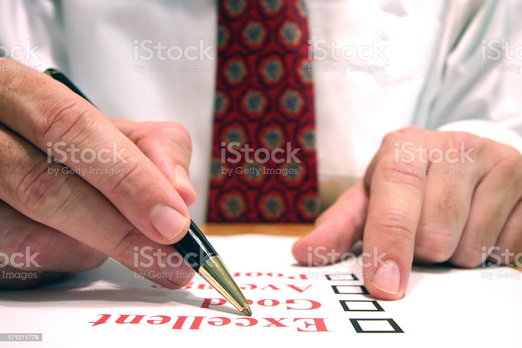A man is filling out paper work with a pen royalty-free stock photo