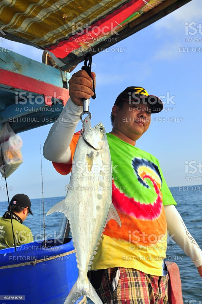 man is fishing queenfish by hook for entartainment stock photo