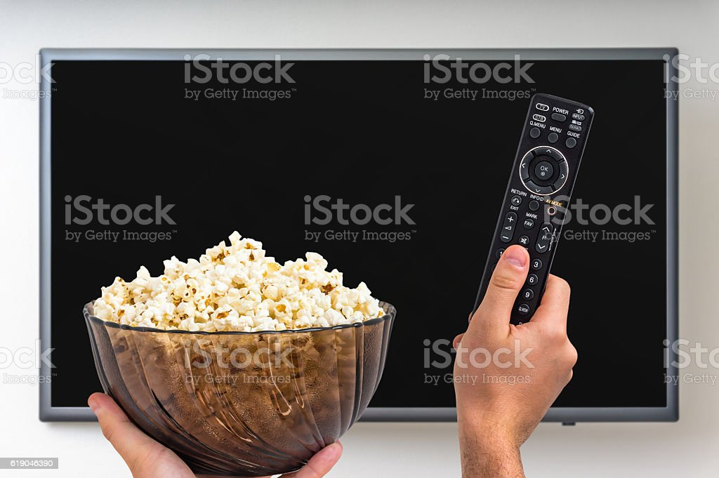Man is going to switch on TV stock photo