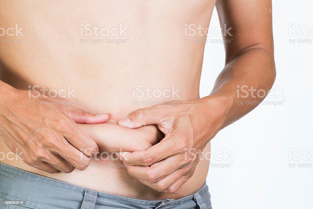 man is grabbing a love handle around her waist stock photo