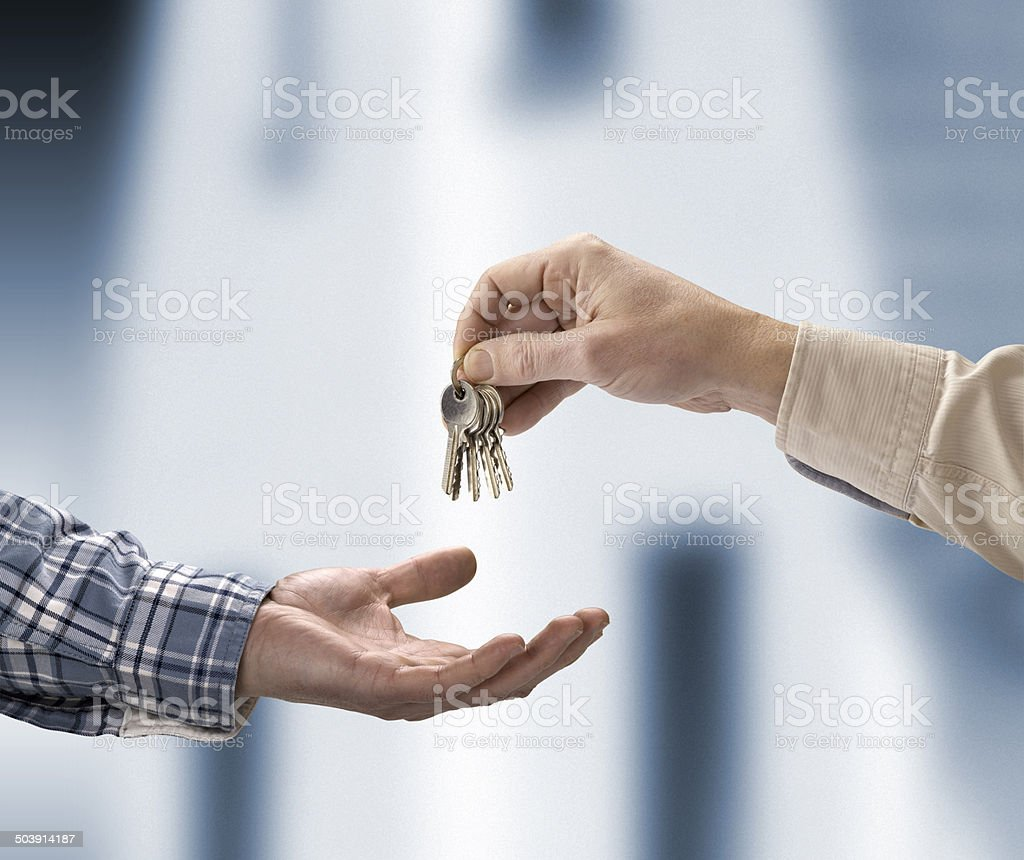 Man is handing house key to a other stock photo
