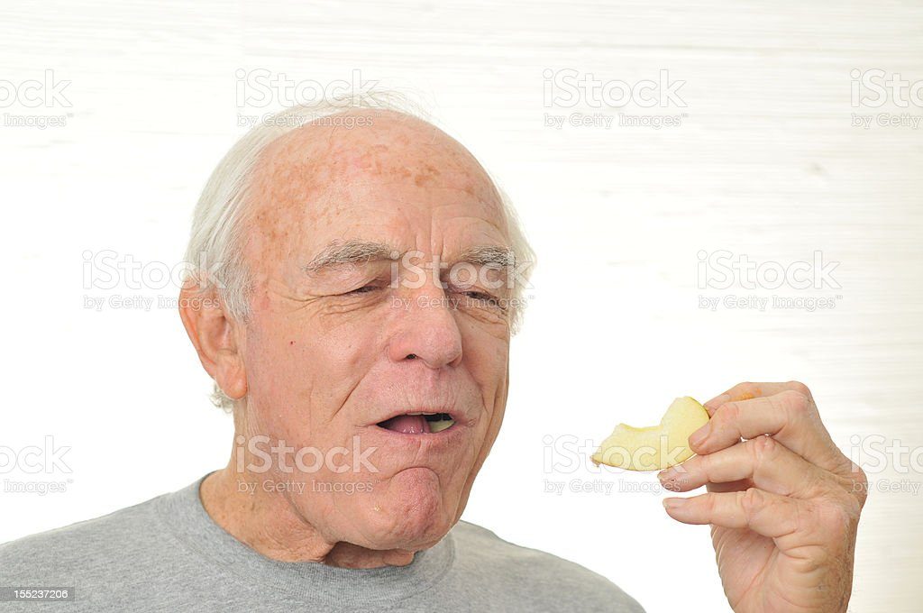 Man is happy eating a slice of apple stock photo
