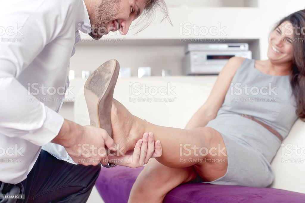 Man is helping his wife out of High Heels shoes stock photo