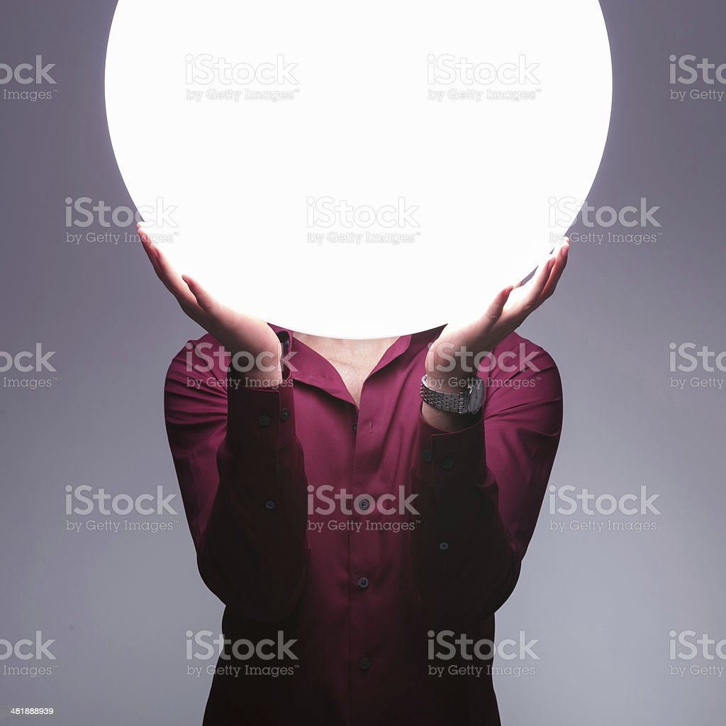 man is holding big sphere of light over his face stock photo