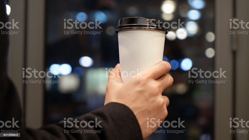man is holding paper coffee cup with a brown plastic cap stock photo