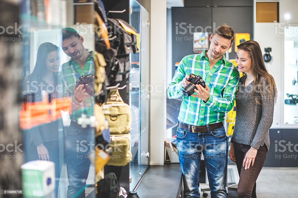Man is holding SLR camera in the store stock photo